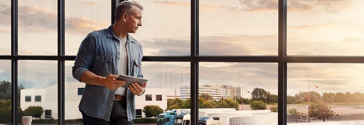 Tahvelarvutit hoidev mees seisab akna juures ja vaatab alla oma veokipargi poole